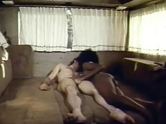 A naked guy is laying on his back on a couch in the back of a caravan. A black girl comes up to him and kisses him, massaging his dick at the same time. She climbs on top of him and shoves his hard on all the way into her pussy.